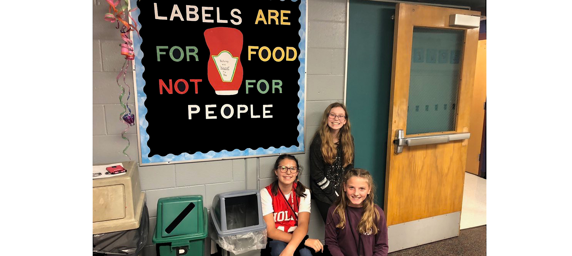 Sign saying Labels are for food, not people and three girls sitting near it