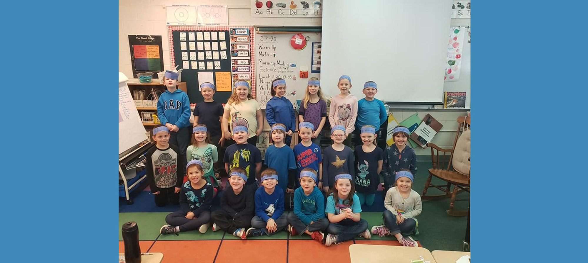 Students in class with head bands that say Autism Awareness