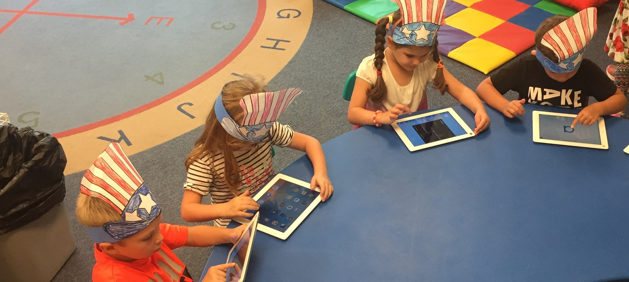 Students working on iPads with hats on that look like flags