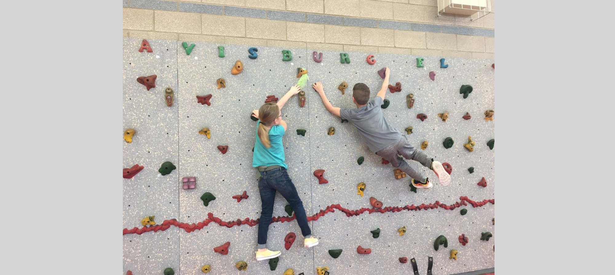 Two students climbing on the climbing wall in the gym.