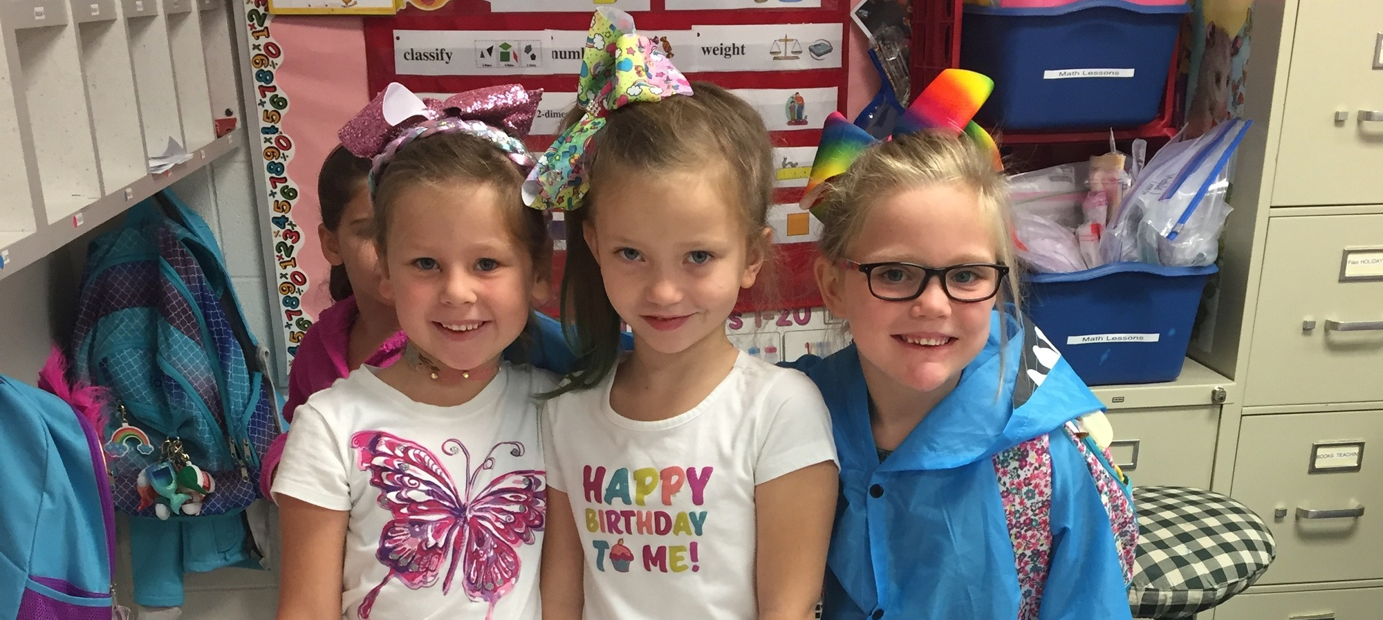 Three girls with bows in their hair.