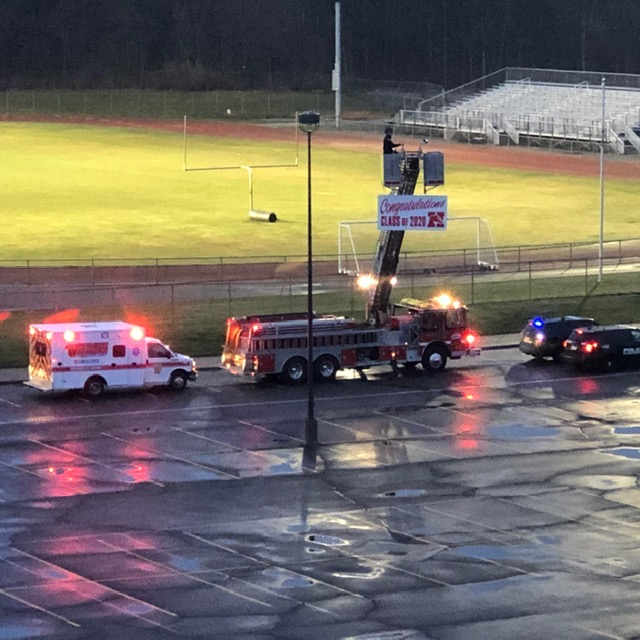 Fire truck with sign - congratulations Class of 2020, police car and ambulance with lights going lined up by the field with the lights on.