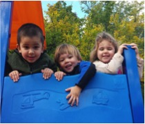 Three student at the top of a blue slide